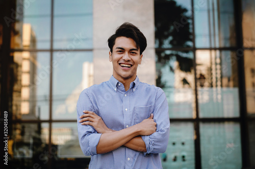 Fototapeta Happy Young Businessman Standing with a Big Smile in the City. Crossed Arms and Looking at Camera obraz