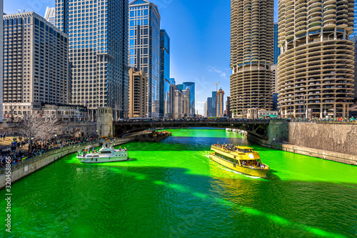 fototapeta na ścianę Chicago building and cityscape on Saint Patrick's day around Chicago river walk with green color dyeing river in Chicago Downtown, illinois, USA, crowned irish and american people are celebrating.