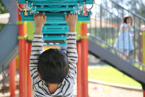 Fototapeta boy climbing monkey bars at playground obraz