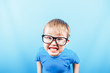 Leinwanddruck Bild - Funny boy in glasses looking at camera and show teeth, back to school.