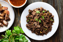 Northern Thai Food, Spicy Minced Pork Salad (Larb Moo Kua) Eating With Grilled Intestine And Fresh Vegetables On Wooden Background, Top View