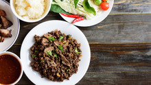 Northern Thai Food, Spicy Minced Pork Salad (Larb Moo Kua) Eating With Sticky Rice, Grilled Intestine And Fresh Vegetables On Wooden Background, Top View