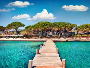 Magnificent summer view of wooden pier on Santa Giulia beach. Romantic morning scene of Corsica island, France, Europe. Splendit Mediterranean seascape. Beauty of nature concept background..
