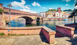 Leinwanddruck Bild Sunny spring cityscape of Bosa town with Ponte Vecchio bridge across the Temo river. Captivating morning view of Sardinia island, Italy, Europe. Traveling concept background..