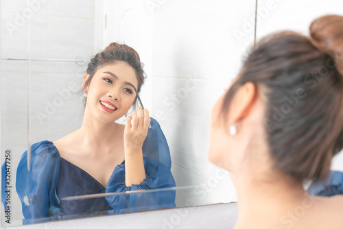 Portrait of a beautiful asian woman as applying makeup near a mirror Wallpaper Mural