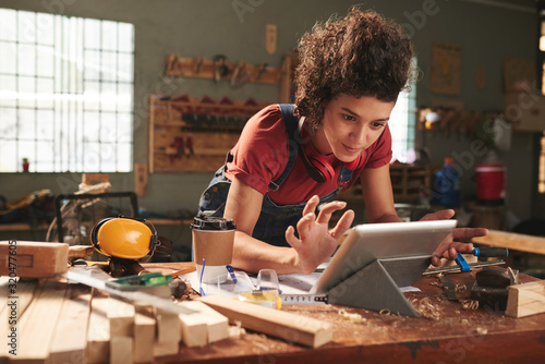 Photo Young pretty woman with curly hair watching woodworking tutorial on digital tabl