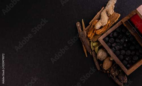 Photo Top view closeup of black ayurvedic tablets in a wooden box with assorted whole spices on a black background