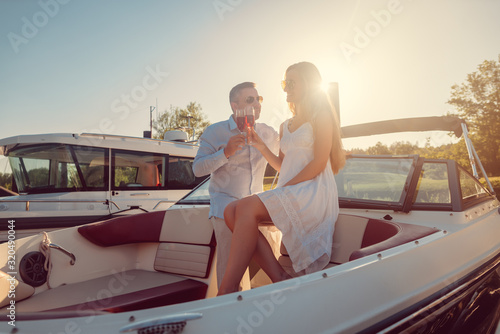 Couple in a river boat or yacht toasting with sparkling wine Obraz na płótnie