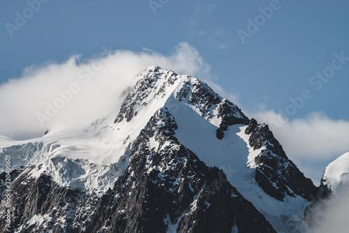 Fényképezés Atmospheric minimalist alpine landscape with massive hanging glacier on snowy mountain peak