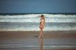 Young slim beautiful woman stay and posing in the sea or ocean waves