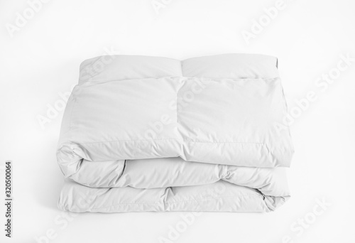 Folded soft white duvet, blanket or bedspread, against white background Wallpaper Mural