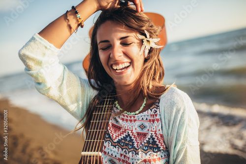 Smiling girl walking on the beach holding a guitar in her hands. - 320501001