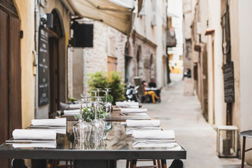Outdoor restaurant in Italy. Empty glasses set in cafe with beautiful italian street at the background. Food, travel and vacation concept