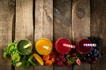 Fototapeta Do baru Selection of colorful smoothies and ingredients in glasses, rustic background