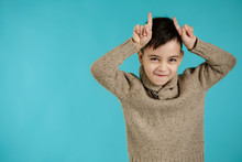 Happy Funny Little Child Boy Doing Funny Gesture With Finger Over Head As Bull Horns On Blue Background. Facial Expression