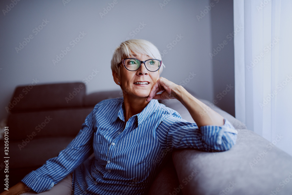 Fototapeta Portrait of smiling charming caucasian blond woman sitting on sofa in living room next to window and looking trough it.
