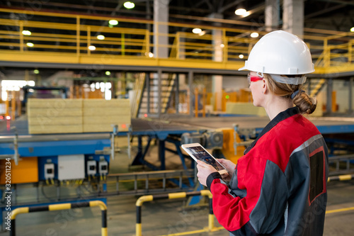 Rear view of busy woman in hardhat and safety goggles using tablet while controlling production line process at factory - 320511234