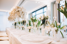 Formal Luxury Elegant Wedding Decor Restaurant Tables Served White Tablecloth, Plates, Menus, Glasses, Tulips In Vases, Orchids, Candles Silver Chairs, Blue Background