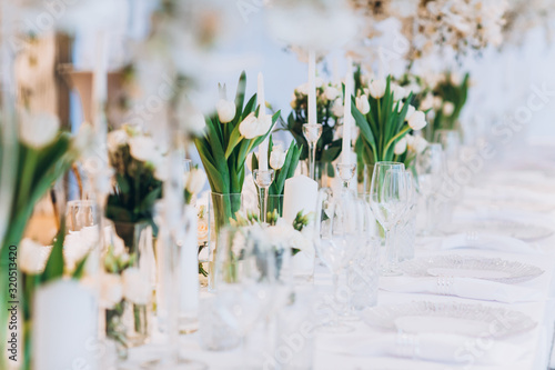 Obraz formal luxury elegant wedding decor restaurant tables served white tablecloth, plates, menus, glasses, tulips in vases, orchids, candles silver chairs, blue background - fototapety do salonu