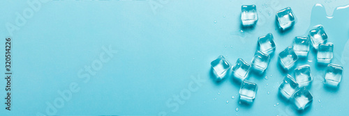 Ice cubes with water on a blue background. Ice concept for drinks. Banner. Flat lay, top view