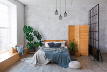 Cozy Bedroom Area At Luxury Studio Apartment With A Free Layout In A Loft Style With Big Panoramic Window And Green Plant.