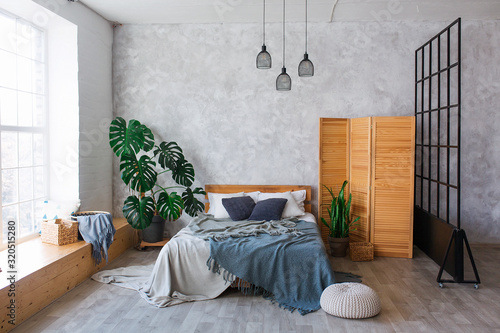 Fototapeta Cozy bedroom area at luxury studio apartment with a free layout in a loft style with big panoramic window and green plant