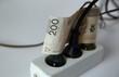 Biały przedłużacz elektryczny z trzema wpiętymi czarnymi wtyczkami, pomiędzy kalblami przewinięte 200 złotych, koncept wzrostu cen / wysokich opłat za elektryczność