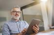 Leinwanddruck Bild - Mature man in office working with digital tablet