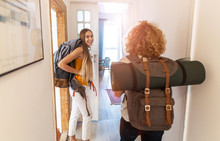 Young Women With Backpacks Arriving To A Youth Hostel
