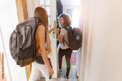 Young women with backpacks arriving to a youth hostel  - 320526470