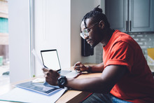 Concentrated Young Black Businessman Reading Documents And Using Laptop In Office