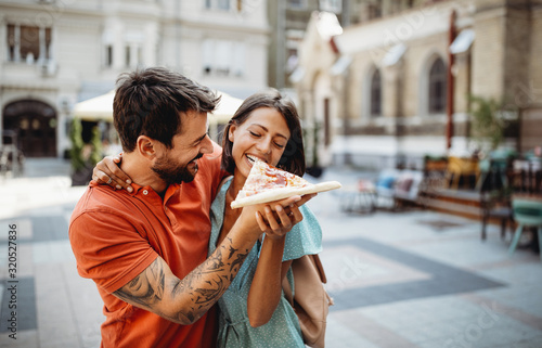 Happy couple eating pizza while traveling on vacation