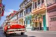 Leinwandbild Motiv Vintage classic red american car in a colorful street of Havana, Cuba.