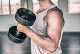 Gym fitness workout fit man training biceps muscles with free weights lifting dumbbells for arm workout.
