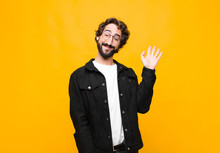 Young Crazy Handsome Man Smiling Happily And Cheerfully, Waving Hand, Welcoming And Greeting You, Or Saying Goodbye Against Orange Wall
