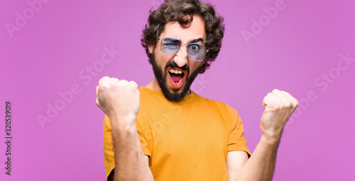 Obraz young crazy cool man shouting aggressively with an angry expression or with fists clenched celebrating success against flat wall - fototapety do salonu