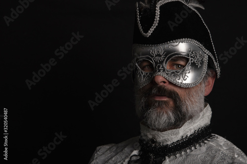 Man with mask, hat, Venetian shirt and beard on black background Canvas Print