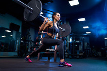 Woman Doing Squats Using Barbe...