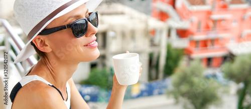 Fotografia, Obraz Elegant beautiful woman drinking coffee or tea with resort summer urban view