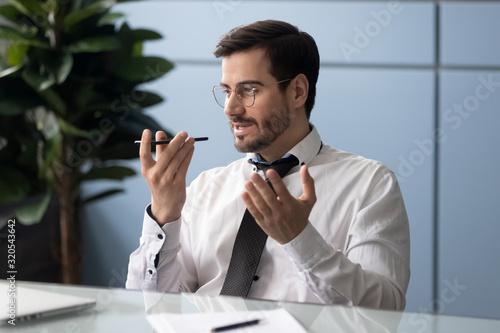 Businessman holding smartphone speaking through microphone sending voice message Canvas Print