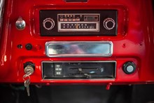 Vintage Radio In Dashboard Of Red Classic Car