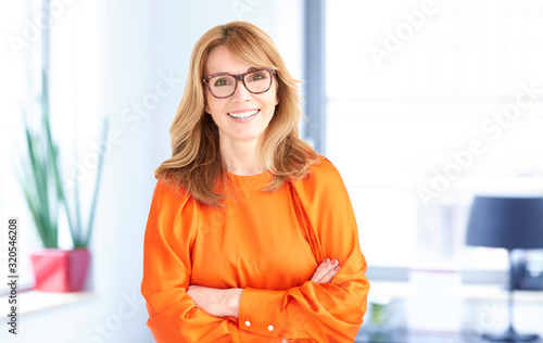 Portrait of middle professional woman with toothy smile standing in the office Wallpaper Mural