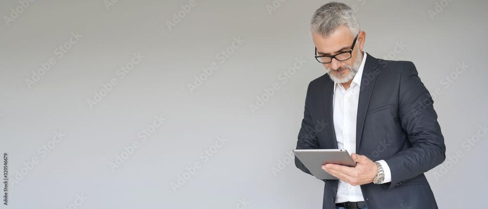 Fototapeta Businessman using digital tablet isolated on background- template