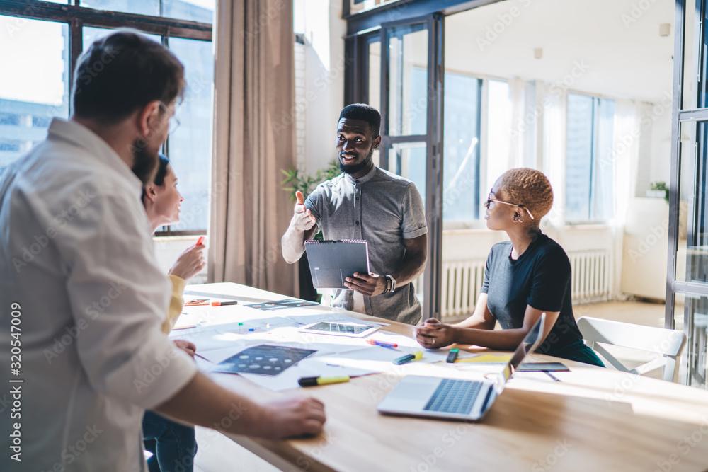 Fototapeta Black man speaking with colleagues during meeting