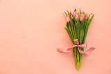 Fototapeta Tulips - Fresh flower composition, bouquet of bi color tulips, pale pink and white gradient background. International Women's day, mother's day greeting concept. Copy space, close up, top view, flat lay.
