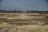 Fototapeta Sawanna - samochody terenowe w oddali na polnej drodze pomiędzy wyschniętymi trawami afrykańskiej sawanny z górami w tle