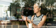 Thoughtful Casual Caucasian Woman Holding Mobile Phone While Looking Through The Coffee Shop Window During Coffee Break. Street Reflections In The Window Glass.