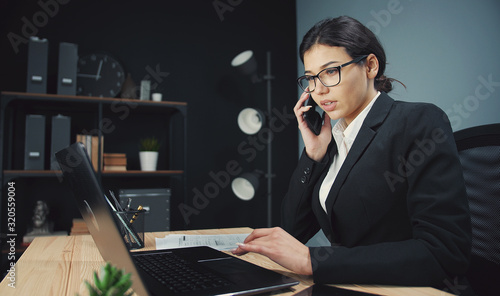 Photo Occupied business lady in formal attire and spectacles talking smartphone while