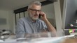 Architect working in office on desktop, talking on phone