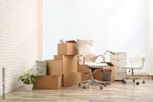 Moving boxes and stuff near white brick wall in room